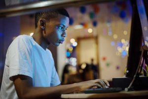 African american boy using a computer at night