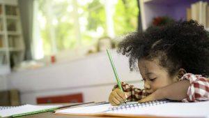black girl doing homework in a notebook