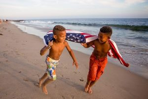 black boys running on the beach with the american flag blowing in the wind behind them