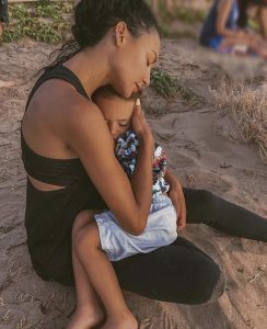 Naya Rivera cradling her son in her arms while sitting in the sand on the beach