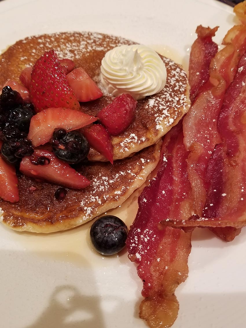 Short Stack Buttermilk Pankcakes with Virginia Maple syrup, honey butter, powdered sugar, macerated seasonal berries, mint, and thick-cut slab bacon