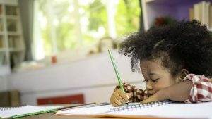 black girl doing homework in a notebook