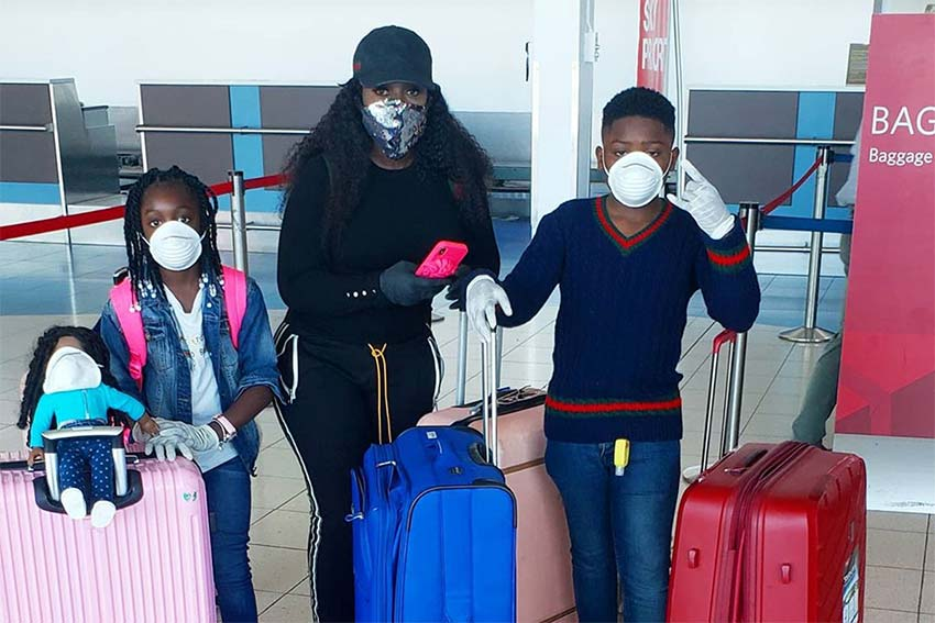 Spice and her children pictured in the Airport with masks, luggage, and gloves.