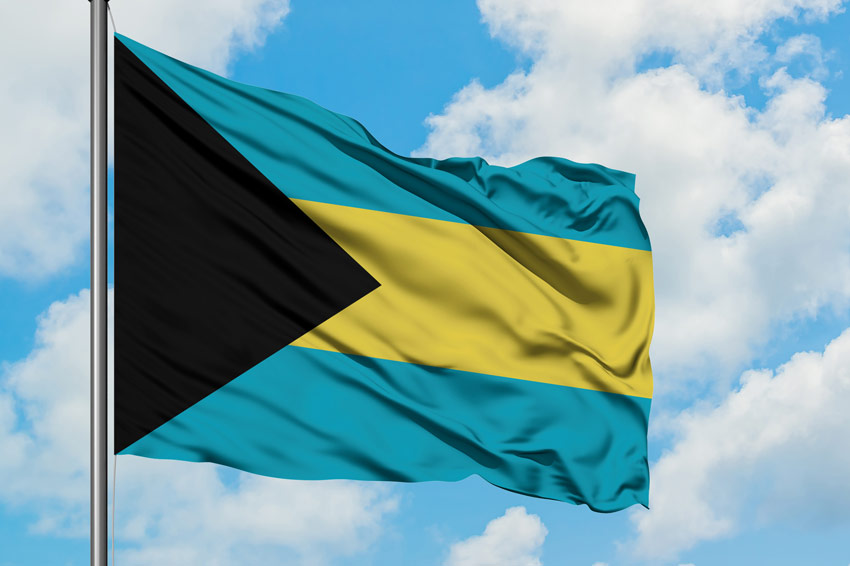 flag of the bahamas flying against a blue sky with clouds