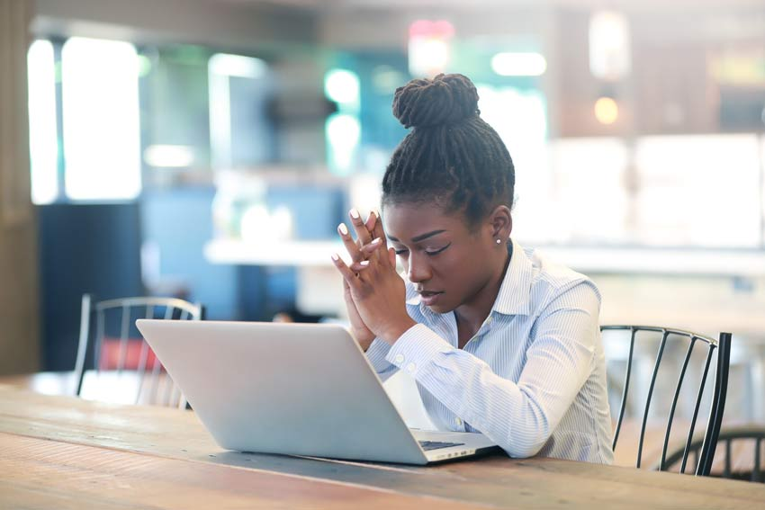 black women with her head down and eyes closed in front of her laptop in an office breakroom
