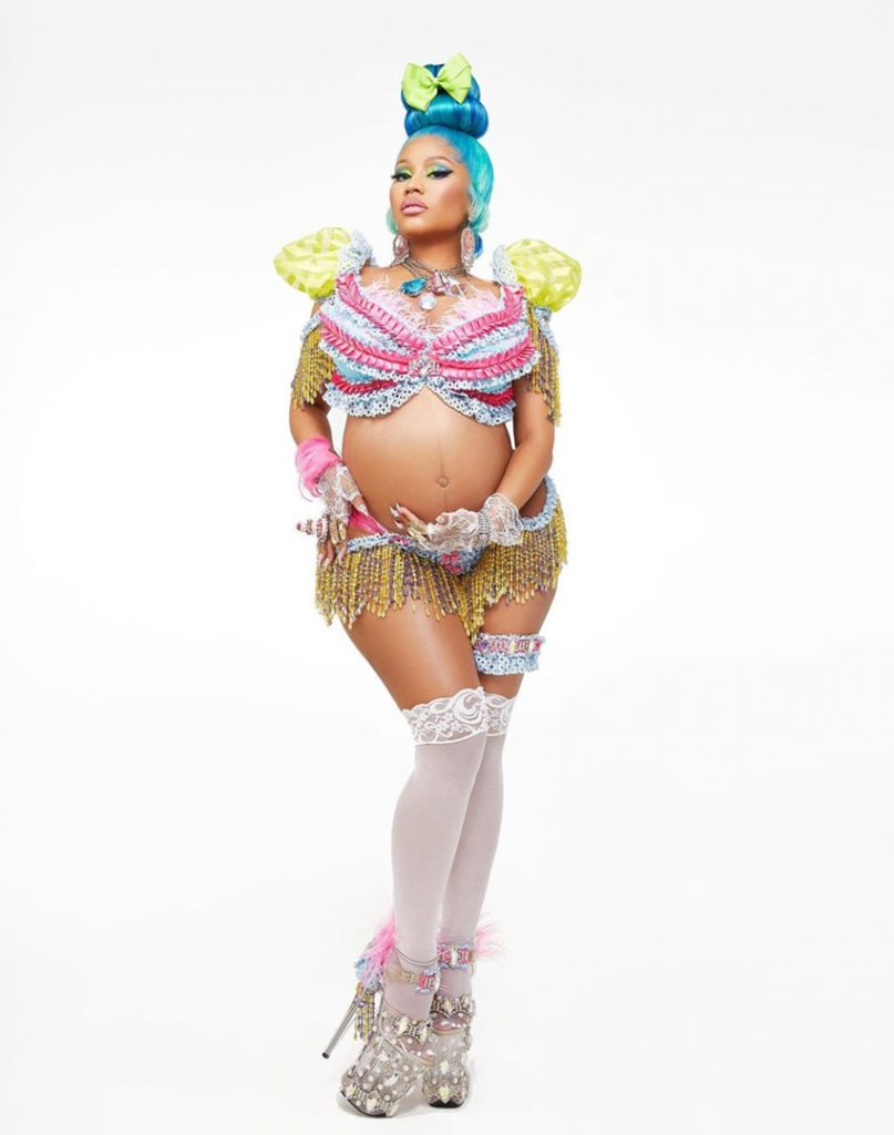 Nicki Minaj is standing in platform heels with turquoise hair and a bikini with knee socks cradling her pregnant belly