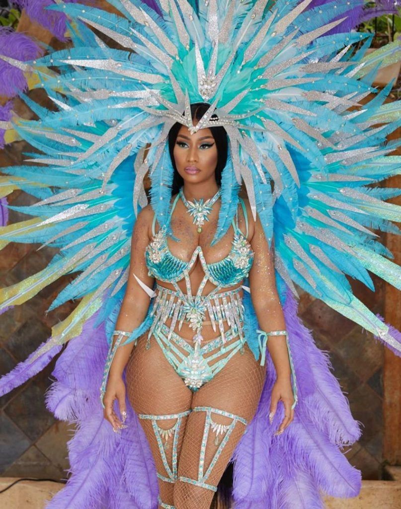 nicki minaj is wearing a blue and purple carnival costume with several plumes of feathers attached to the bikini style two piece jewel covered costume