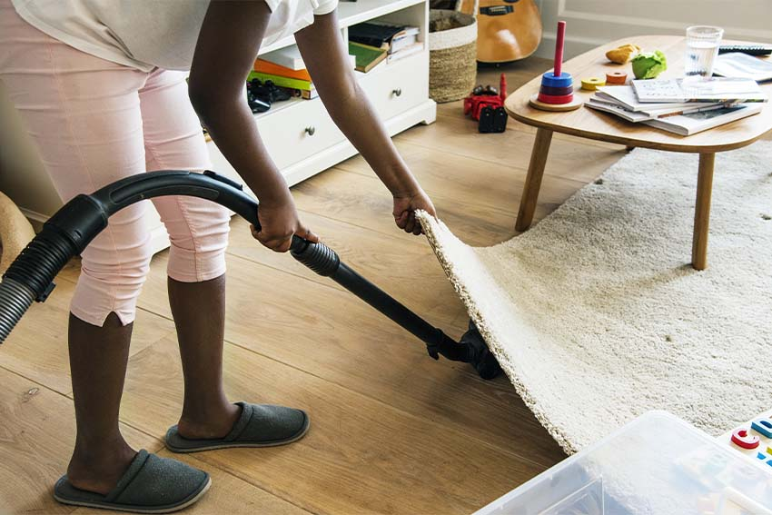 black child lifting a rug to vacuum