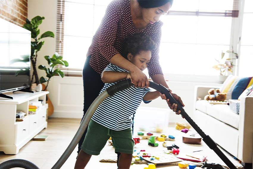 black mother helping son vacuum