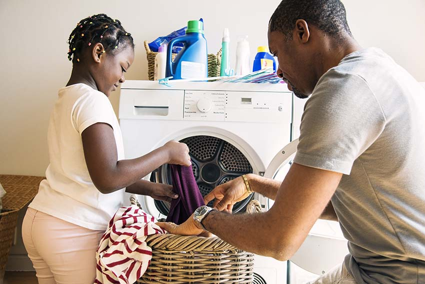 black girl helping father wash clothes