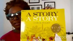 eva wilson holding up a book with a yellow cover titled a story a story